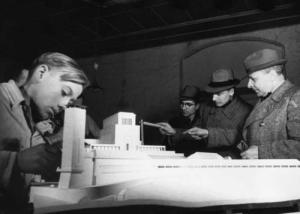 Helt til høyre i bildet ser vi arkitekt Clemens Klotz som forklarer den neste fase av utvidelser ved førerskolen i Ordensburg Vogelsang. Førerskolen ligger noen mil i vestlig retning fra hans eget arkitektatelier i Köln.